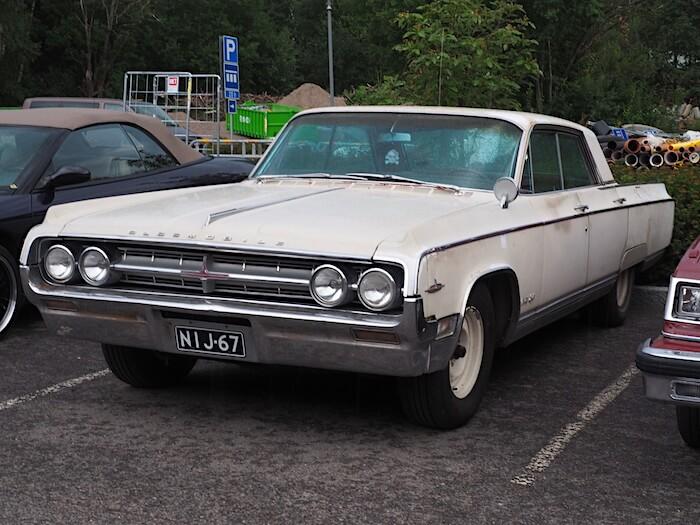 Valkoinen 1964 Oldsmobile Ninety-Eight 4d Sedan Suomi-auto. Kuvan tekijä: Kai Lappalainen. Lisenssi: CC-BY-40.