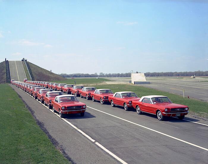 Vuosimallin 1964 punaisia Ford Mustangeja jonossa tekstiradalla. Kuvan copyright: Ford Motor Company.