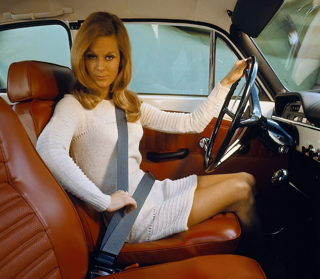 Kolmipisteturvavyö ja nainen Volvo P130 Amazon autossa. Tekijä ja copyright: Volvo Car Corporation.
