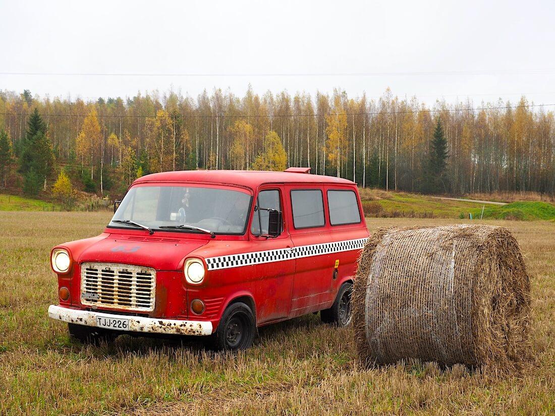 Punainen 1975 Ford Transit heinäpellolla