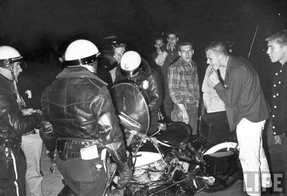 Poliisi sakottaa laittomiin kiihdytyskilpailuihin osallistuneita nuoria vuonna 1957.