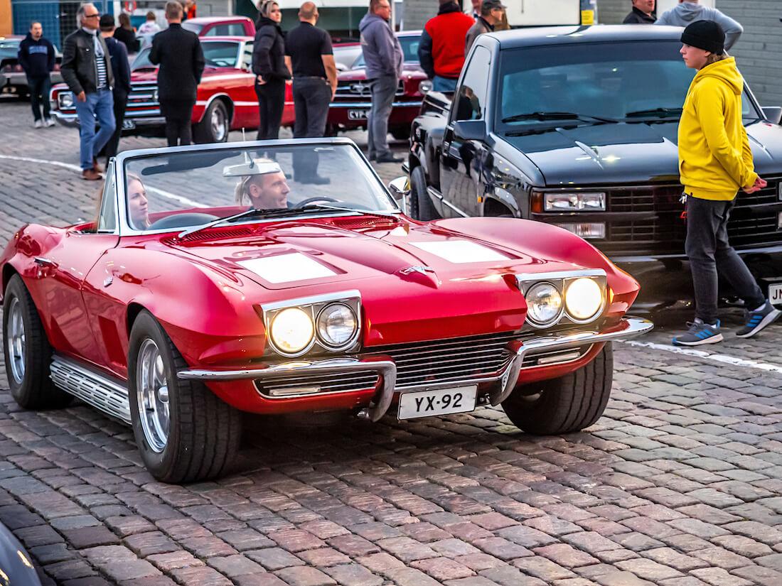 Nainen ja mies punaisessa 1963 Chevrolet Corvette Stingray jenkkiautossa
