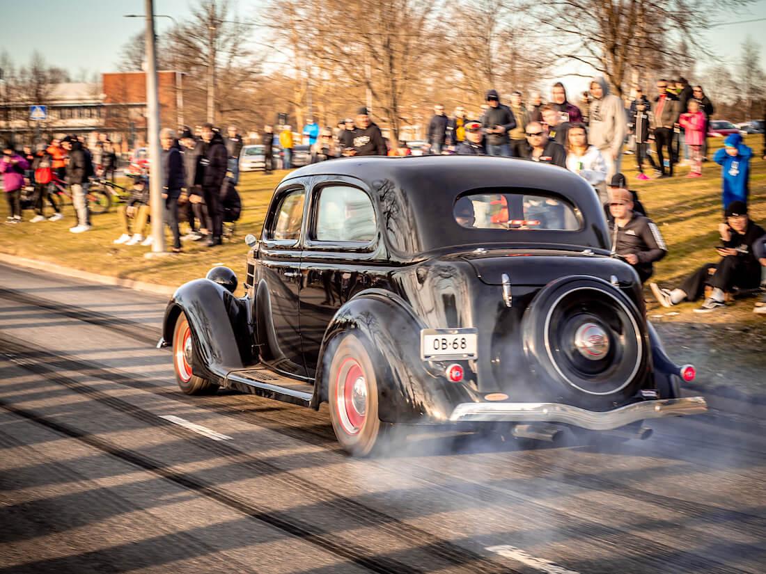 Musta 1936 Ford Tudor jenkkiauto kiihdyttää