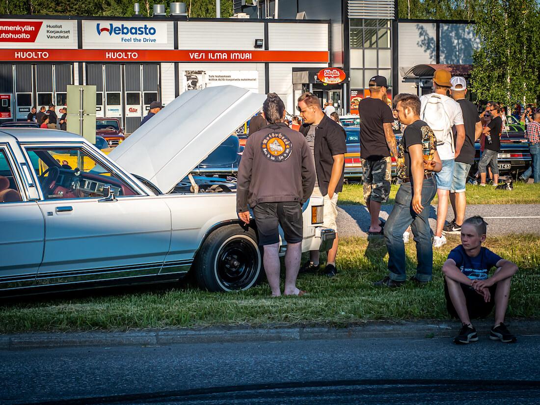 Nuoret miehet tutkivat jenkkiauton moottoria
