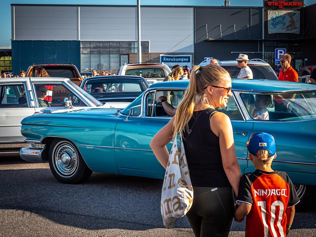 Nainen ja poika ihailee jenkkiautoja